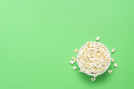 Bowl with popcorn on a green background. Flat lay, top view Stock Photo