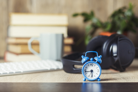 Alarm clock, headphones and keyboard on the office desk with books. Office concept, work day, hourly pay, work schedule, work in a call center