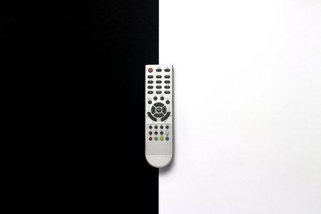 Gray remote control on a black and white background. The concept of television, movies, TV shows, sports, day and night, 24 7, for adults, for children. Flat lay, top view