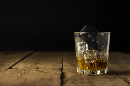Car keys in a glass with an alcoholic drink on a wooden background. Drunk driving concept, stop drinking and driving