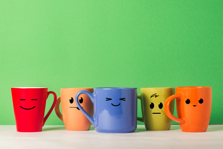 A lot of multicolored cups with funny faces on a green background. The concept of a friendly company, a big family, meeting friends for a cup of tea or coffee, father's day, office, boss day Фото со стока
