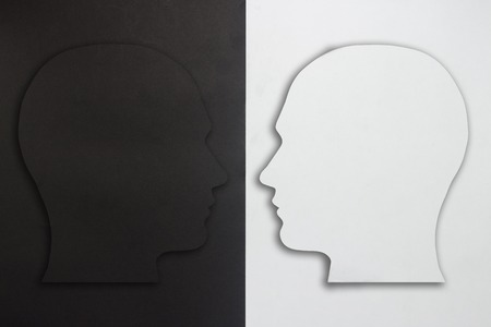 Two paper heads, black and white on a black and white background. The concept of a split personality, different opinions, dispute, war. Flat lay, top view