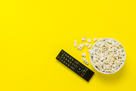A bowl of popcorn and TV remote on a yellow background. The concept of watching TV, film, TV series, sports, shows. Flat lay, top view