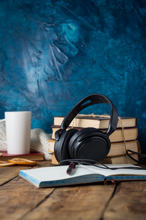 Books are stacked, Headphones, White Cup, open Diary on a wooden background. The Concept of Audio Books. Stock Photo