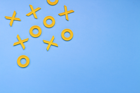 Yellow plastic crosses and zeroches for playing tic-tac-toe on a blue background. Concept XO Win Challenge. Developmental game for children. Flat lay, top view.