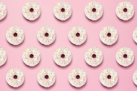 Fresh tasty sweet donuts on a pink background. The concept of fast food, bakery, breakfast, sweets. Minimalism. Pattern. Flat lay, top view 免版税图像