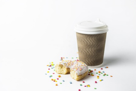 A paper cup with a lid, coffee or tea to go and fresh tasty donuts and sweet multicolored decorative candies on a white background. Bakery concept, fresh pastries, delicious breakfast, fast food