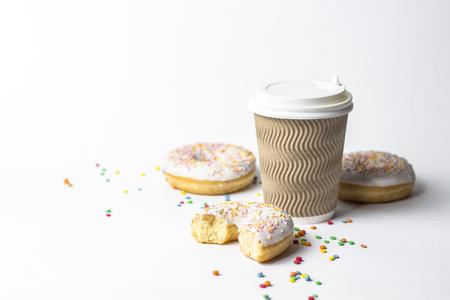 Una taza de papel con tapa, café o té para llevar y rosquillas frescas y sabrosas y dulces dulces decorativos multicolores sobre un fondo blanco. Concepto de panadería, pasteles recién hechos, delicioso desayuno, comida rápida
