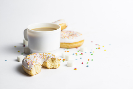 White Cup, coffee or tea with milk and fresh tasty donuts, sweet multicolored decorative candy on a white background. Bakery concept, fresh pastries, delicious breakfast, fast food