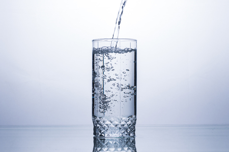 Glass is filling with a stream of clean and refreshing water on a white background. Concept of quenching thirst and cooling drinks in hot weather. Water balance and daily water consumption