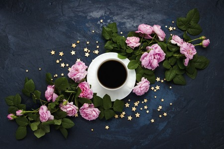 White cup with black coffee, stars and pink roses on a dark blue background. Concept of coffee with flowers and the night sky. Flat lay, top view.