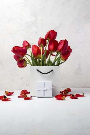 White Gift bag, small white gift box and bouquet of red tulips on a light stone background. Concept Offers an engagement or marriage.