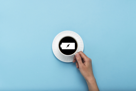 Female hand holding a white cup with black coffee on a blue background. Sign of a charged battery. Concept charge for the day. Flat lay, top view. Stock Photo