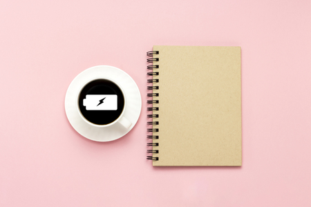 White cup with black coffee, notebook on a pink background. Sign a charged battery. Concept charge for the day. Flat lay, top view. Stock fotó