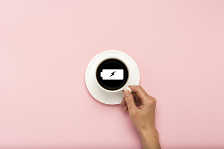 Female hand holding a white cup with black coffee on a pink background. Sign of a charged battery. Concept charge for the day. Flat lay, top view. Stock Photo