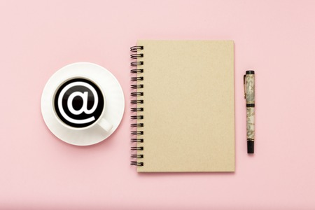 White cup with black coffee, notebook, pen on a pink background. Sign email. Flat lay, top view.