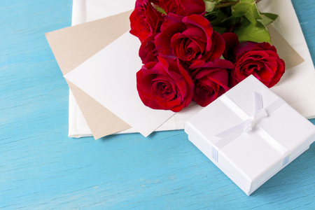Bouquet of red roses White gift box clean sheet, blue wood background. Copy space. Romantic gift for Valentines Day holiday.