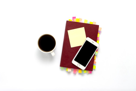 Red diary with stickers on the pages, a cup with black coffee, telephone, white background. Concept of a successful business, a lot of meetings and plans for a long period. Flat lay, top view.