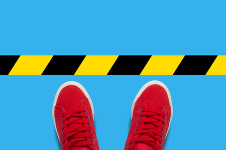 Female feet in red sneakers standing in front of a warning black-and-yellow line. Concept of the destruction of borders and violations of the rules. Flat lay, top view Stock Photo