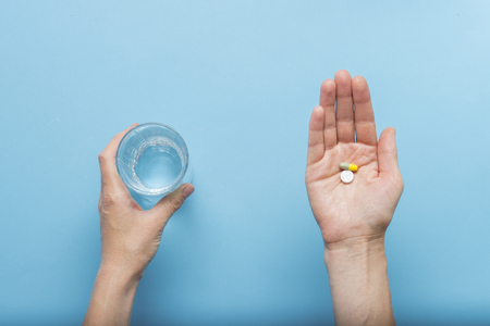 Female hand is holding a pill in the palm of a hand while the second hand is holding a glass of water on a blue background. Concept of taking drugs in case of illness and disease. Flat lay, top view. Фото со стока