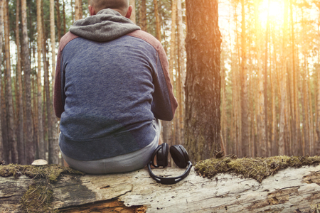 Man sits on fallen tree with his back to the camera and headphones lie down with him in the wild forest. Concept of a hiking trip to the forest or mountains. Sounds of nature and solitude in wild. Imagens