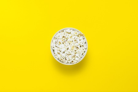 Bowl with popcorn on a yellow background. Flat lay, top view 스톡 콘텐츠