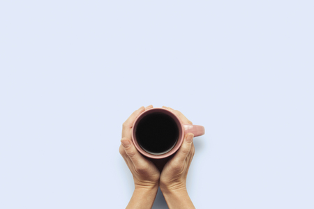 Two hands holding a cup with hot coffee on a blue background. Breakfast concept with coffee or tea. Good morning, night, insomnia. Flat lay, top view.