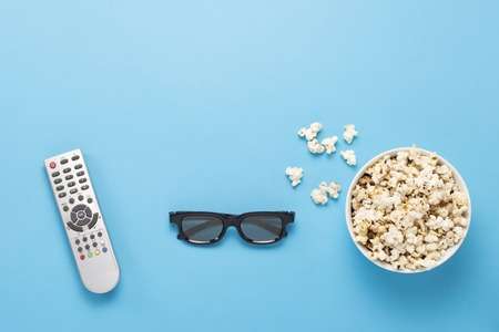 Bowl with popcorn, Imax glasses, remote control for TV on a blue background. Concept home theater, novelties of cinema, leisure. Flat lay, top view.
