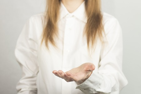 A girl in a white shirt holds in front of her hand palm up. Pose cup