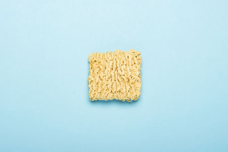 Chinese instant noodles on a blue background. The concept of convenience foods, fast food, junk food. Flat lay, top view