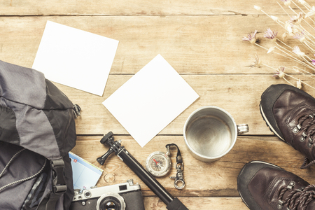 Boots, backpack, compass and other camping gear on a wooden background. The concept of hiking in the mountains or the forest, tourism, tent rest, camp. Flat lay, top view