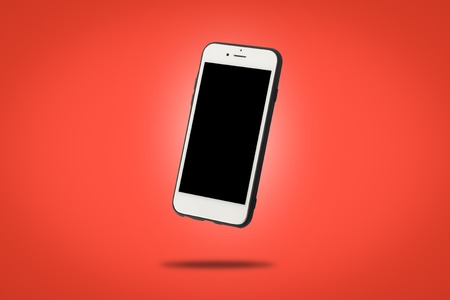 Flying white mobile phone on a red background. Levitation. Concept applications for phone, mobile device, presentation
