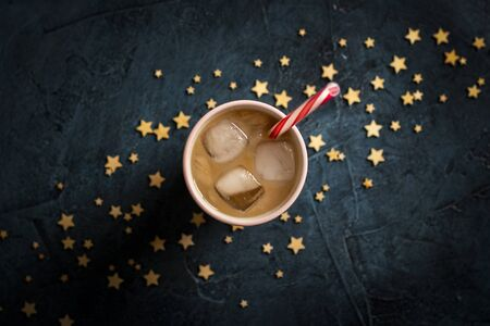 Coffee with ice and milk in a glass on a dark blue stone background with stars. Concept cooling drink, thirst, summer, starry sky, nightlife, insomnia. Flat lay, top view. 写真素材 - 124719570