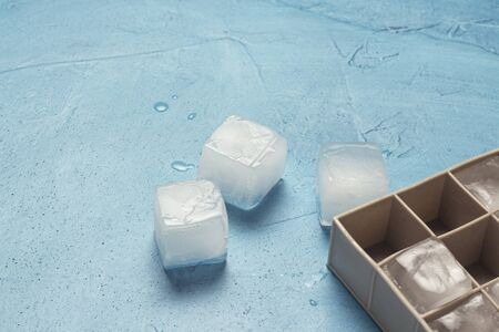 Ice cubes and silicone mold on a blue stone background. Ice production concept. Flat lay, top view. 免版税图像