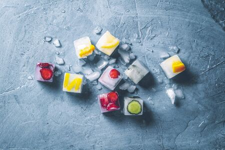 Ice cubes with fruit and broken ice on a stone blue background. Mint, strawberry, cherry, lemon, orange. Flatlay, top view.