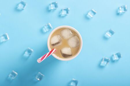 Refreshing coffee with milk and ice in a glass, ice cubes on a blue background. Concept summer, ice, refreshing cocktail, thirst. Flat lay, top view. 写真素材 - 124719623