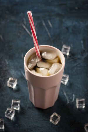 Iced coffee in a glass on a dark blue stone background with ice cubes. Concept cooling drink, thirst, summer, cola with ice, nightlife, club. Flat lay, top view. 写真素材 - 124719624