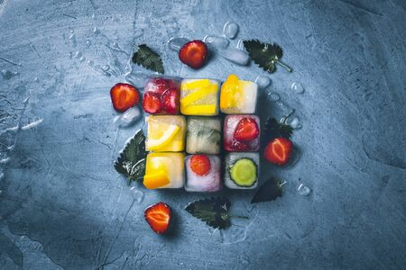 Ice cubes with fruit and broken ice on a stone blue background with mint leaves and fresh fruit. Cube shape. Mint, strawberry, cherry, lemon, orange. Flat lay, top view. Reklamní fotografie