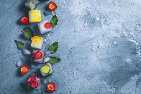 Ice cubes with fruit and broken ice on a stone blue background with mint leaves and fresh fruit. Mint, strawberry, cherry, lemon, orange. Flat lay, top view.