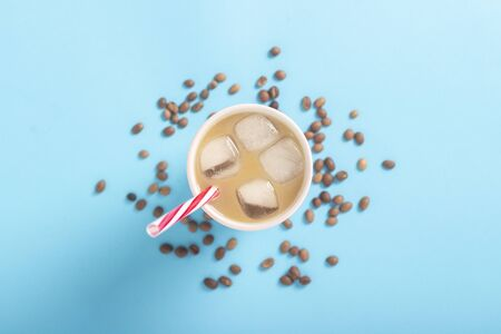 Refreshing coffee with milk and ice in a glass and coffee grains on a blue background. Concept summer, ice, refreshing cocktail, thirst. Flat lay, top view. 写真素材 - 124719635