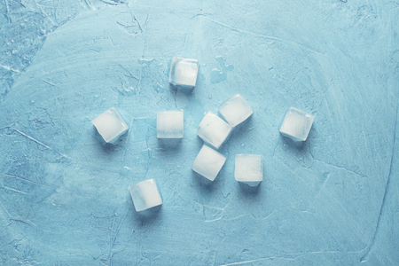 Ice cubes on a blue stone background. Shape of the square. Ice production concept. Flat lay, top view.