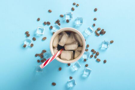 Refreshing iced coffee in a glass and ice cubes and coffee grains on a blue background. Concept summer, cola with ice, refreshing cocktail, thirst. Flat lay, top view. 写真素材 - 124719664