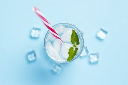 Glass of cold and refreshing water with ice and mint on a blue background. Ice Cube. Concept of hot summer, alcohol, cooling drink, thirst quenching, bar. Flat lay, top view.
