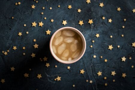 Coffee with ice and milk in a glass on a dark blue stone background with stars. Concept cooling drink, thirst, summer, starry sky, nightlife, insomnia. Flat lay, top view.