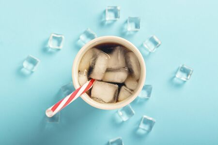 Refreshing iced coffee in a glass and ice cubes on a blue background. Concept summer, cola with ice, refreshing cocktail, thirst. Flat lay, top view. 写真素材 - 124719682