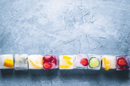 Ice cubes with fruit on a stone blue background. Line. Mint, strawberry, cherry, lemon, orange. Flatlay, top view.