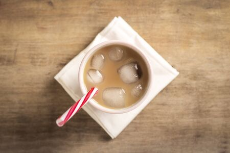 Refreshing and bracing iced coffee in a glass on a wooden background. Concept coffee shop, quenching thirst, summer. Flat lay, top view. 写真素材 - 124719743
