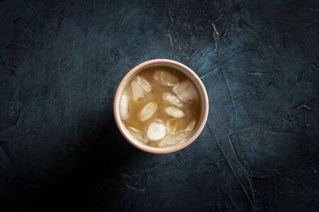 Coffee with ice and milk in a glass on a dark blue stone background. Concept cooling drink, thirst, summer, ice, nightlife, club. Flat lay, top view. 写真素材 - 124719753