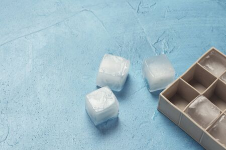 Ice cubes and silicone mold on a blue stone background. Ice production concept. Flat lay, top view. Reklamní fotografie