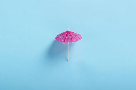 Decorative umbrella for a cocktail on a blue background. Flat lay, top view. Reklamní fotografie